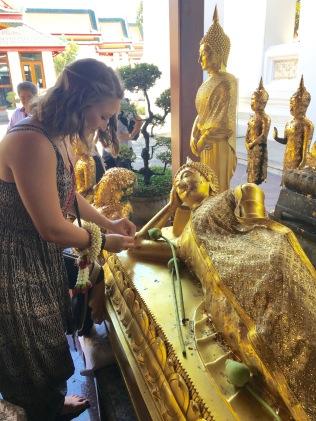 Putting golf lief on a Reclining Buddha in Bangkok, Thailand