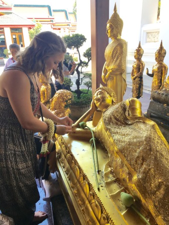 Putting golf lief on a Reclining Buddha in Bangkok, Thailand
